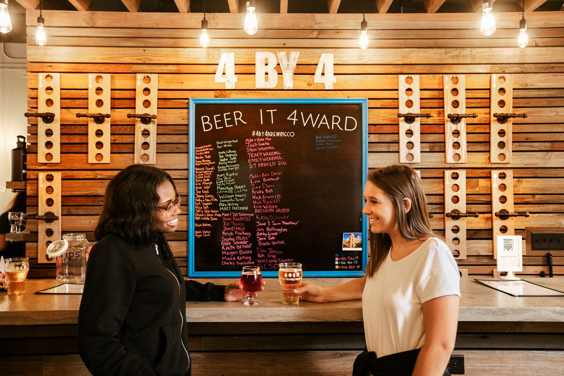 Two women at the bar drinking beer at 4 By 4 Brewing Company