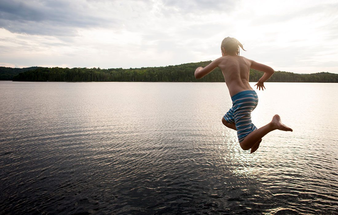 Boy in swim trunks in mid-air jumping into beautiful cove water