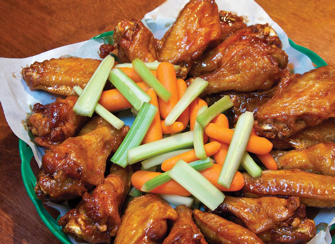 buffalo chicken wings in a basket with carrots and celery