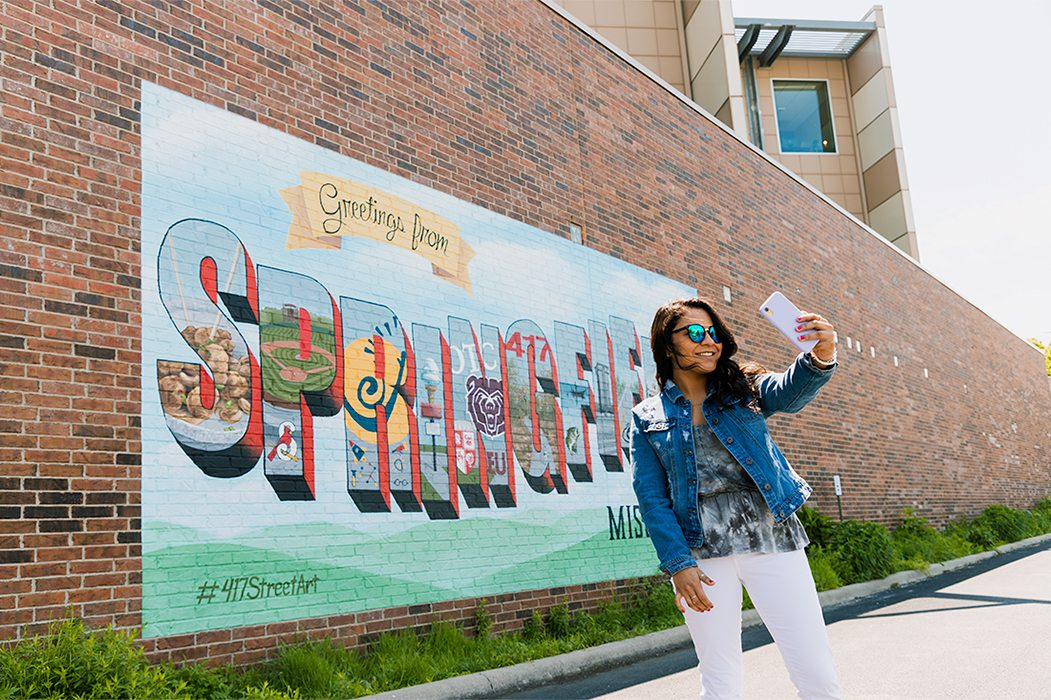Young girl takes a selfie on a beautiful sunny summer day in front of mural in downtown Springfield, MO