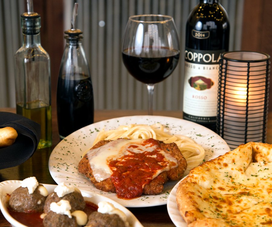 Italian food and wine including meatballs, chicken Parmesan and pizza