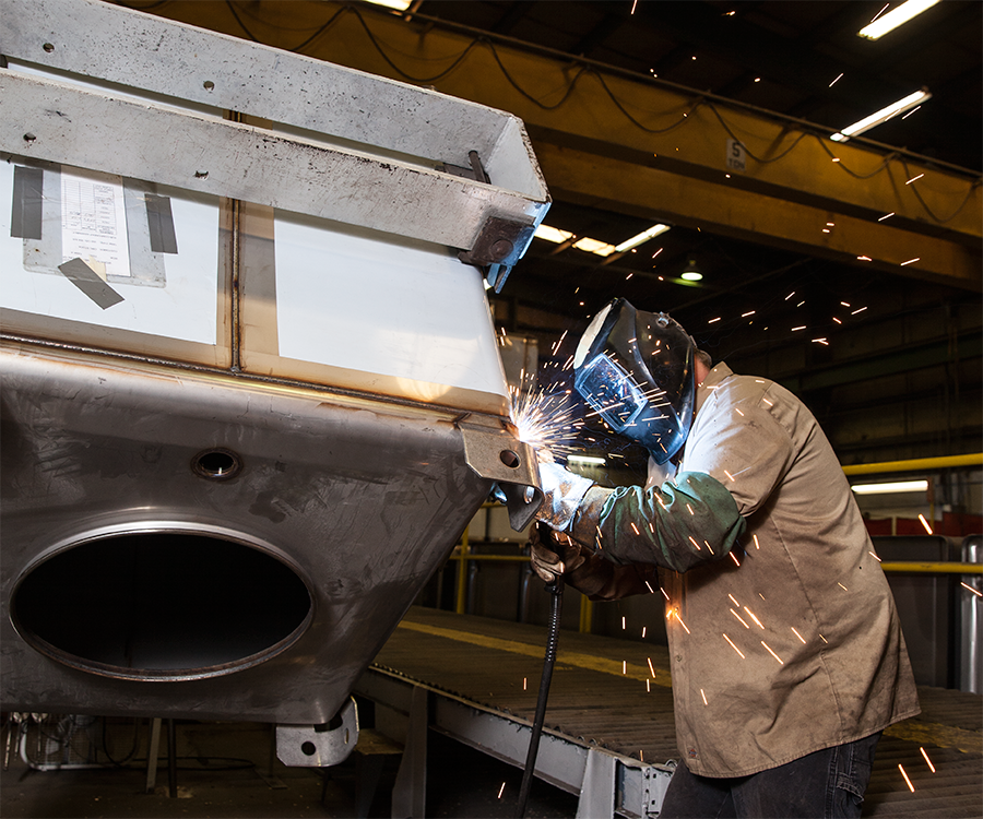 A welder adheres lifting lugs to the top of a Custom Metalcraft tank.