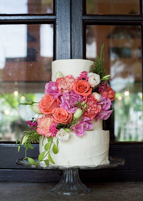 All white wedding cake with bold colored flowers