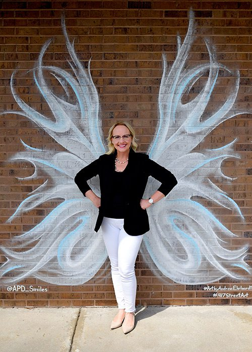 Carrie Arquitt of Arquitt Pediatric Dentistry in front of a mural by Andrea Ehrhardt in Springfield MO