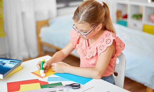 Young girl creating artwork at home