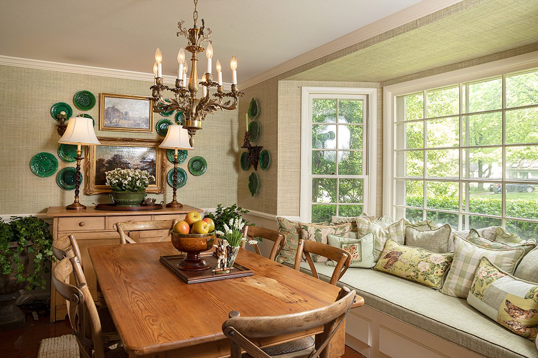 dining room with sage green pillows on window seat and fruit bowl on table with antiques