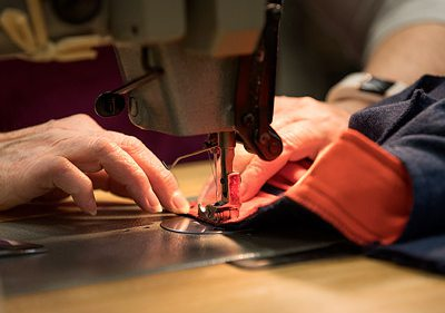 Close up image of hands on a sewing machine.