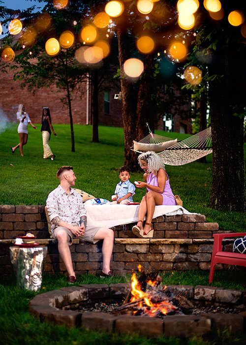 Young family enjoying s'mores by a backyard fire pit