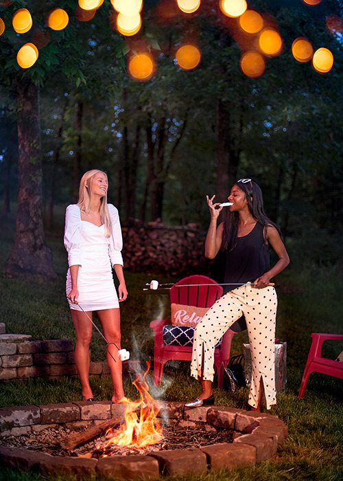 Two young stylish women making s'mores around a backyard fire pit