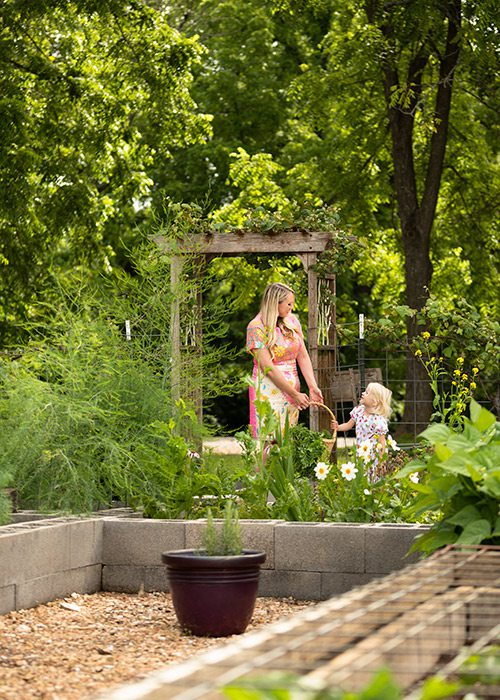 Mother and daughter exploring a large backyard garden