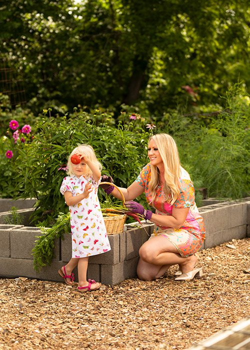 Mother and daughter picking fruits and vegetables in a backyard garden
