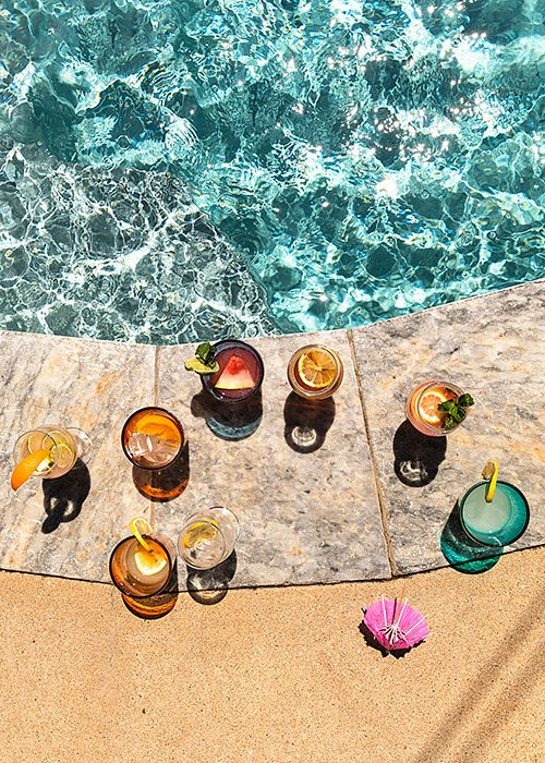 Various cocktails next to an in ground backyard pool