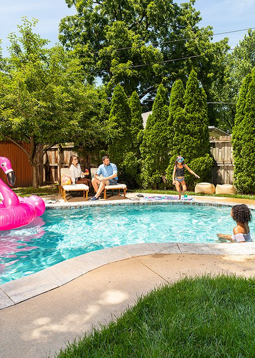 Young families lounging poolside in a backyard