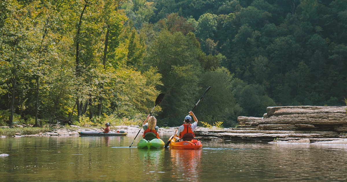 Couple floating in kayaks on the Mulberry River in Arkansas
