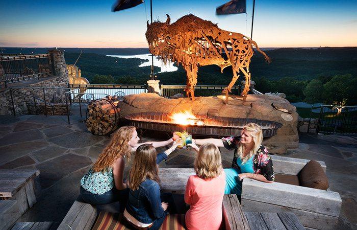 women cheersing drinks over looking the lake