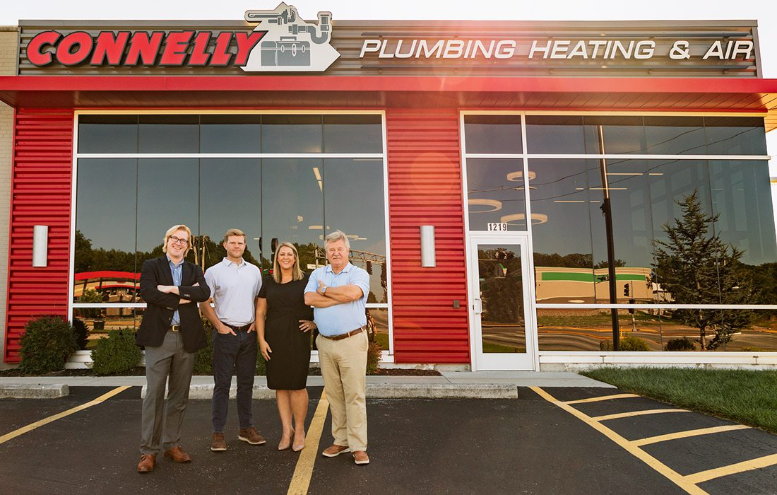 Connelly Plumbing owners stand in front of building