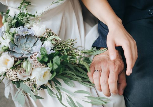 closeup of bride and groom's hands and bridal bouquet