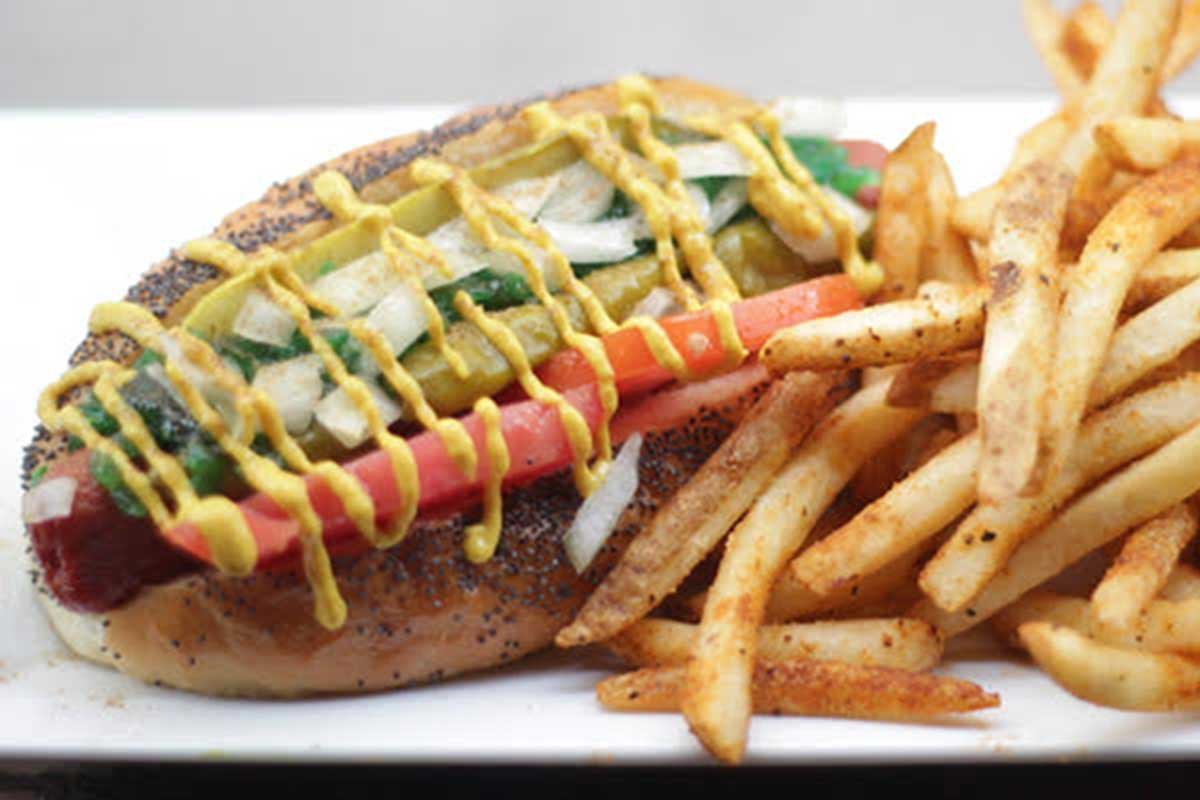 A hot dog covered in veggies and mustard with fries on the side