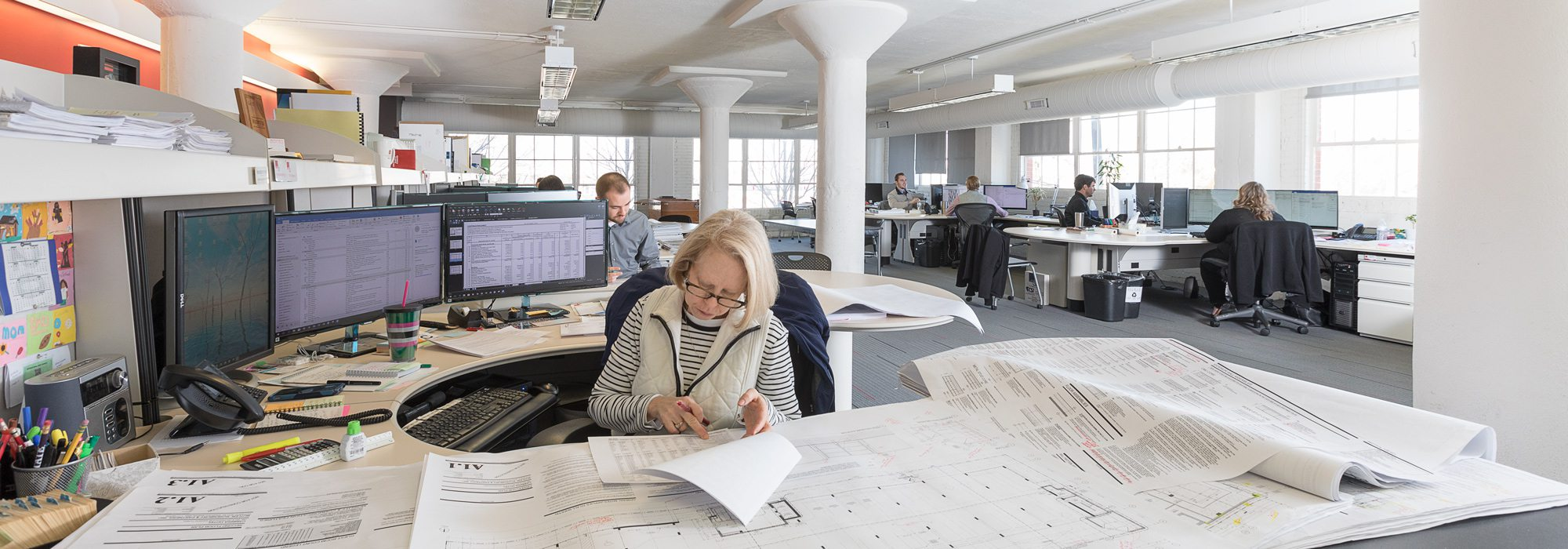 Woman working in open office with architecture plans on desk.