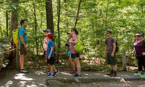 Man giving instructions to a group of people while on a hike in the woods