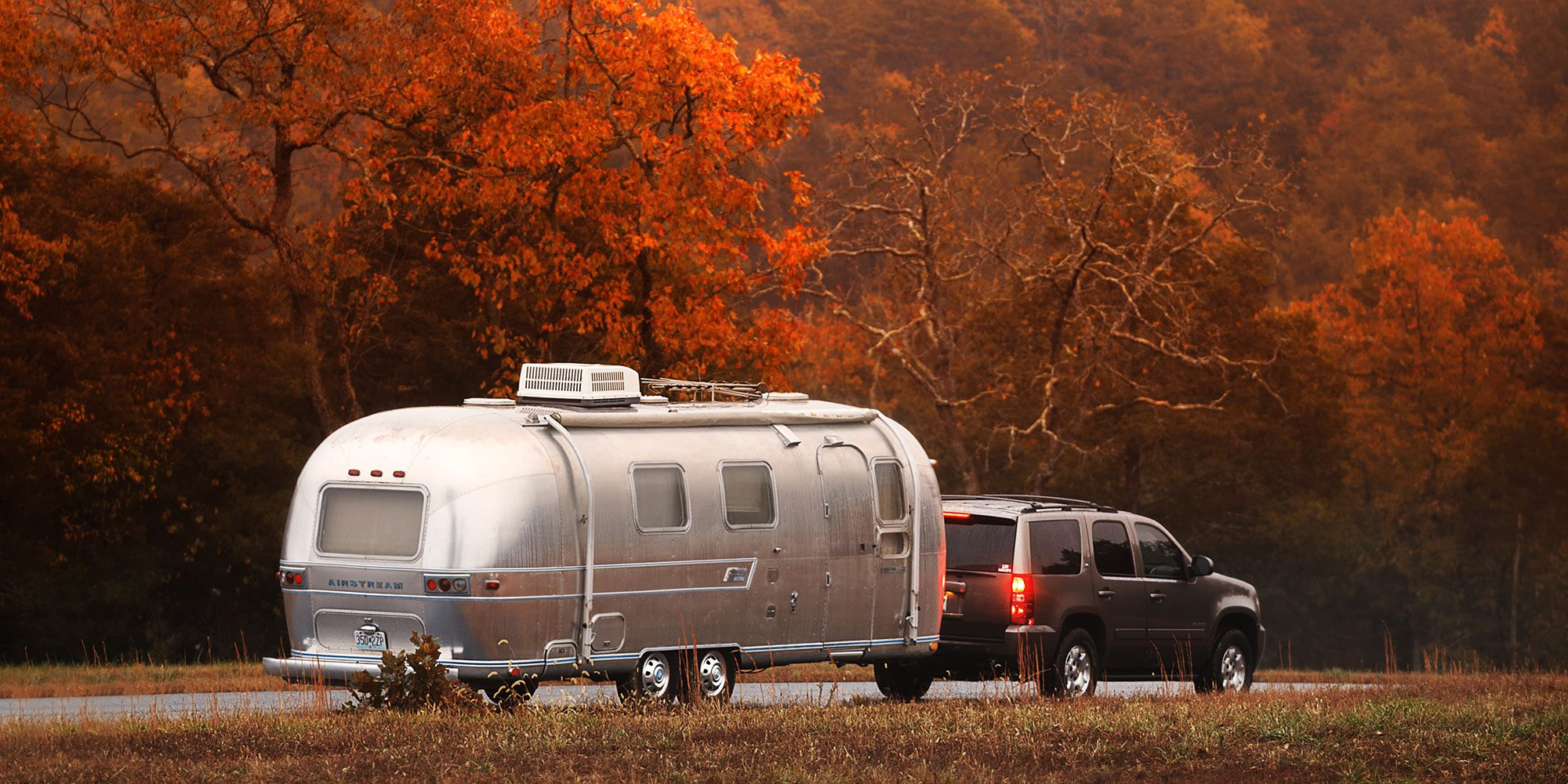 Silver Airstream being pulled down a scenic road with trees full of fall color