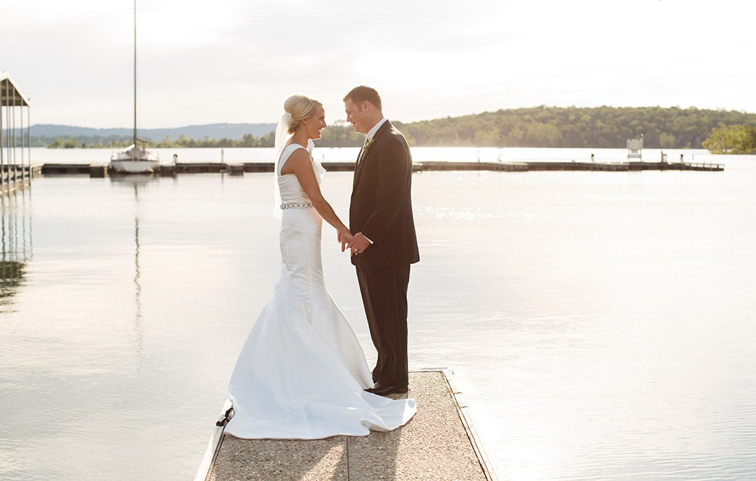 Bride and Groom on a dock at Chateau on the Lake in Branson MO