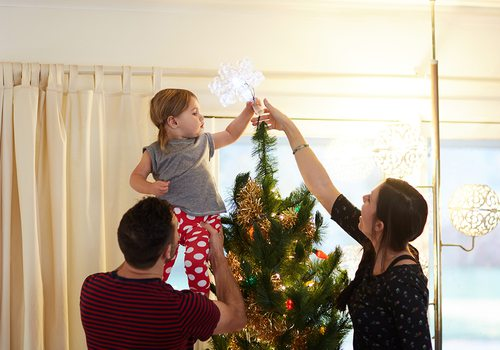 family adding a tree topper on the christmas tree