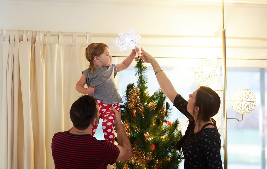 a family decorating a christmas tree
