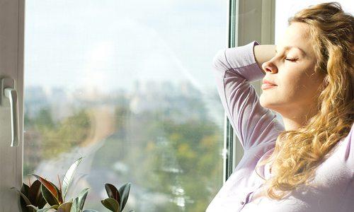 Women breathing in clean air in her home
