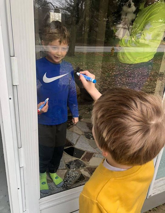 two kids playing tic-tac-toe on a glass door