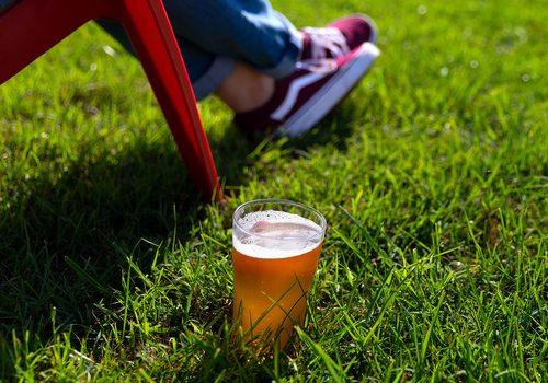 glass of beer in grass by woman's lawn chair at mother's brewery springfield mo