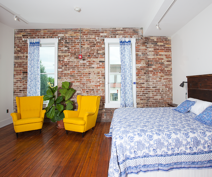 The Jaipur, India room has subtle Indian details and an exposed brick wall housing windows showing a view of C-Street.