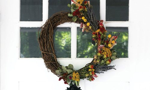 fall wreath hung on a white windowed front door