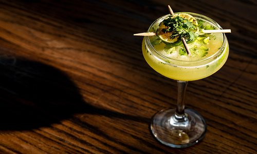 Pineapple and Cilantro gimlet on brown tabletop