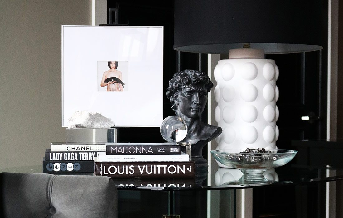 Glass furniture and black and white home decor and coffee table books