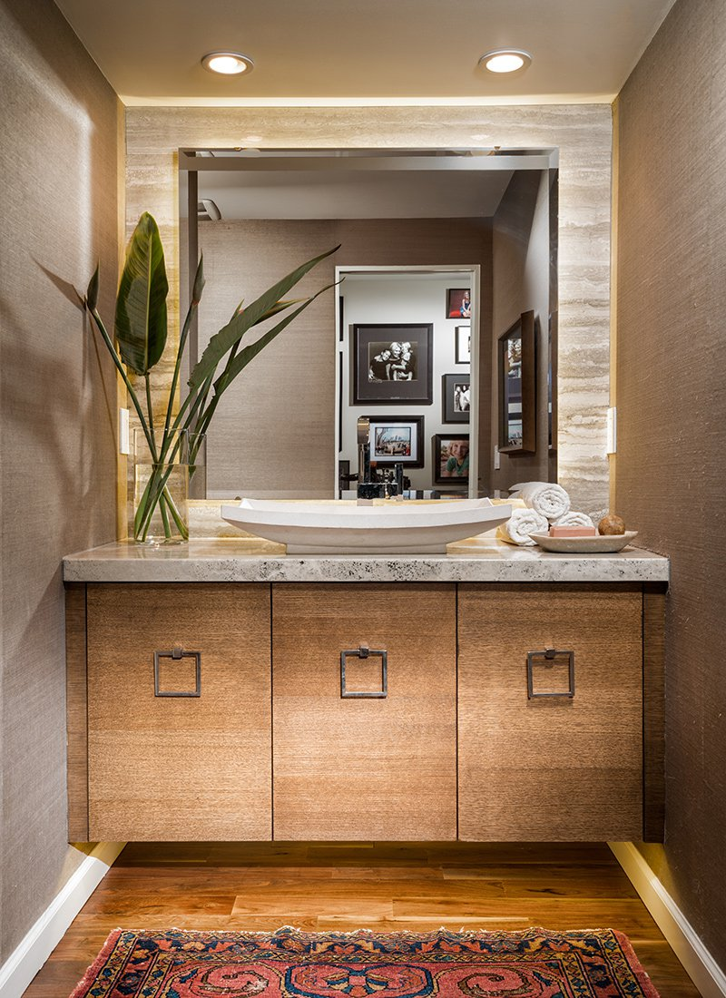 Powder bath with wood cabinets and grass-cloth wallpaper by Nathan Taylor.