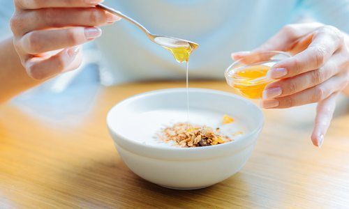 Woman drizzling honey over her bowl of oatmeal