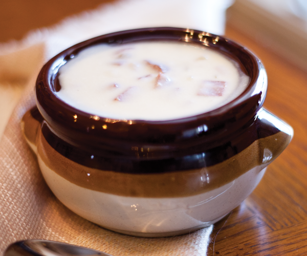 The creamy potato soups sits in a ceramic bowl