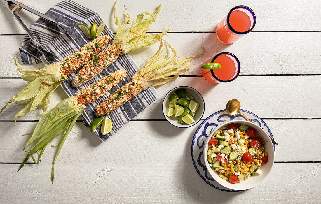 elote and corn salad on blue dishes rest on a white wooden table with drinks and limes