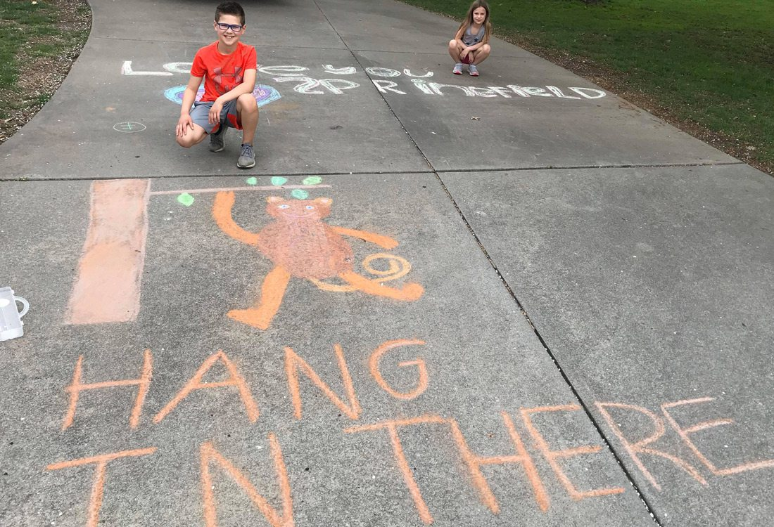 Ryland Matthews and Elise Matthews chalk messages in Emerald Park