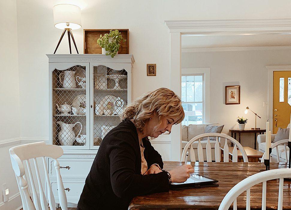 Jen Jeppsen looks at her ipad at her kitchen table