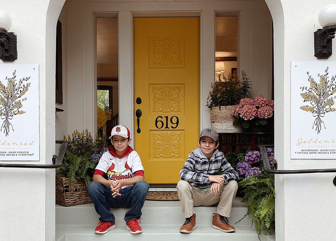 two boys sit outside local shop with yellow door