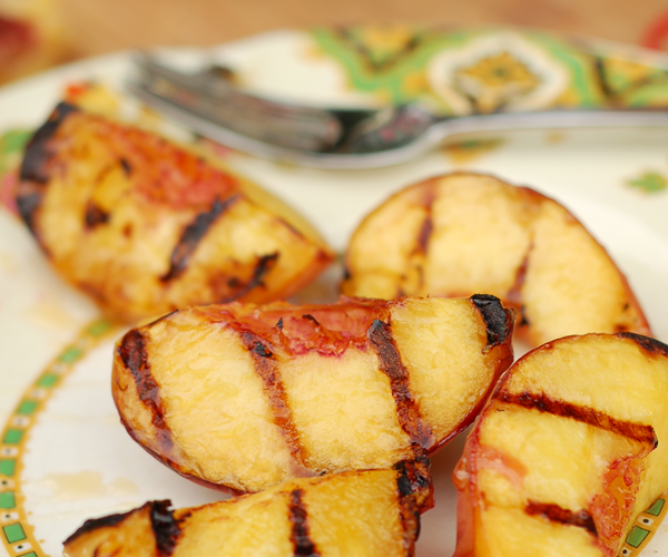 Grilled peaches on a plate.