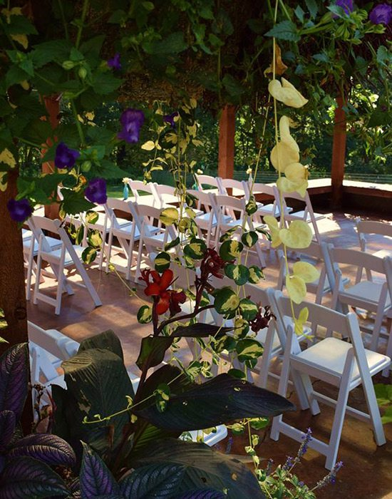 White chairs set for a wedding ceremony at Wheeler Gardens Venue at the Farm in Ozark MO