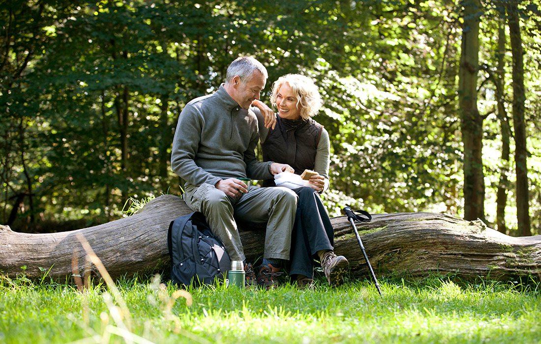 Mature couple enjoying a sandwich while on a hike