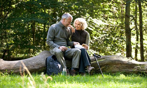 Mature couple enjoying a sandwich while on a hike