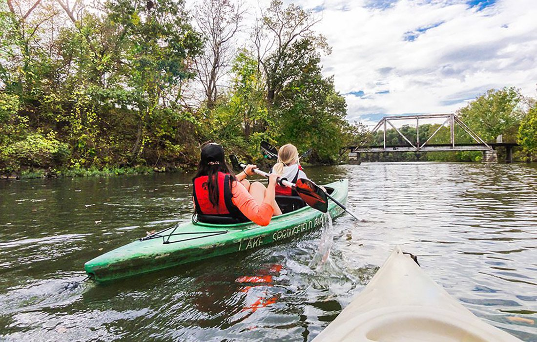 Two girls paddle their kayak down the river towards a bridge on James River in Springfield, MO