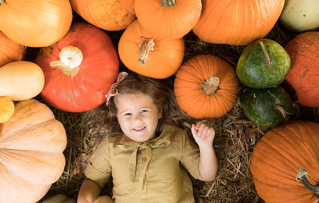 Young girl surrounded by pumpkins at Pickin' Patch Farm