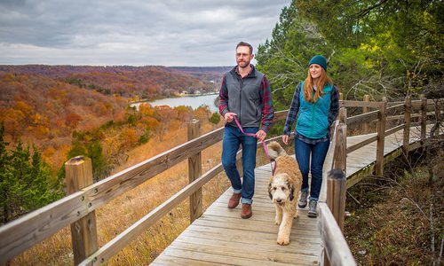 Young couple and their dog on a fall hike in Ha Ha Tonka in Camdenton, Missouri
