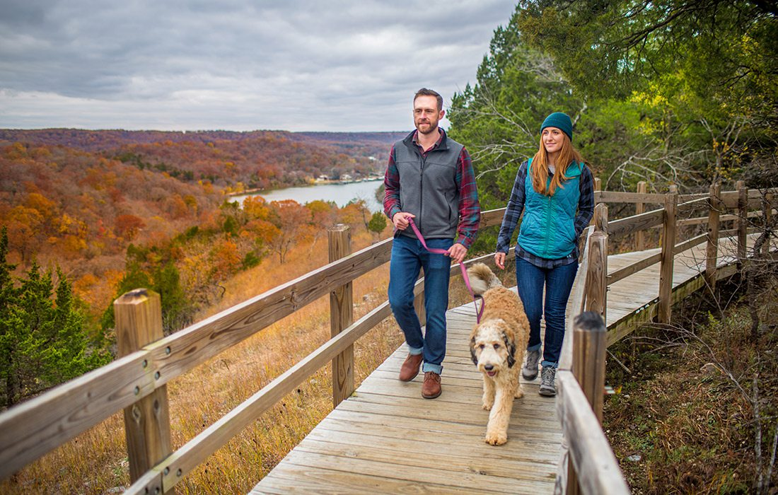 Young couple walking their dog on the Ha Ha Tonka loop trail in Camdenton, Missouri
